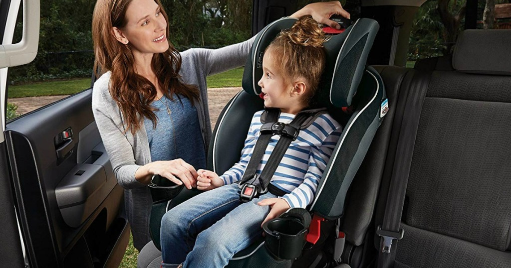 woman adjusting childs car seat, a Graco SlimFit 3 in 1 Convertible Car Seat