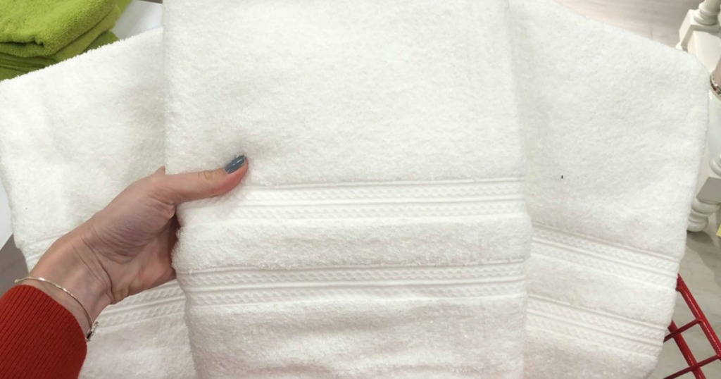 hand holding up home expressions white bath towels from cart