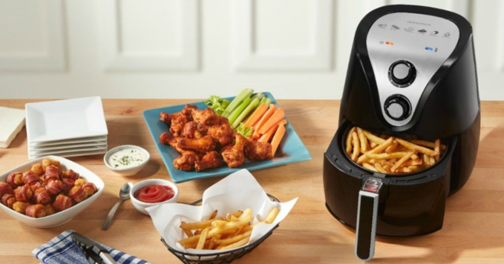 Black air fryer with fries in basket and various appetizers on the countertop