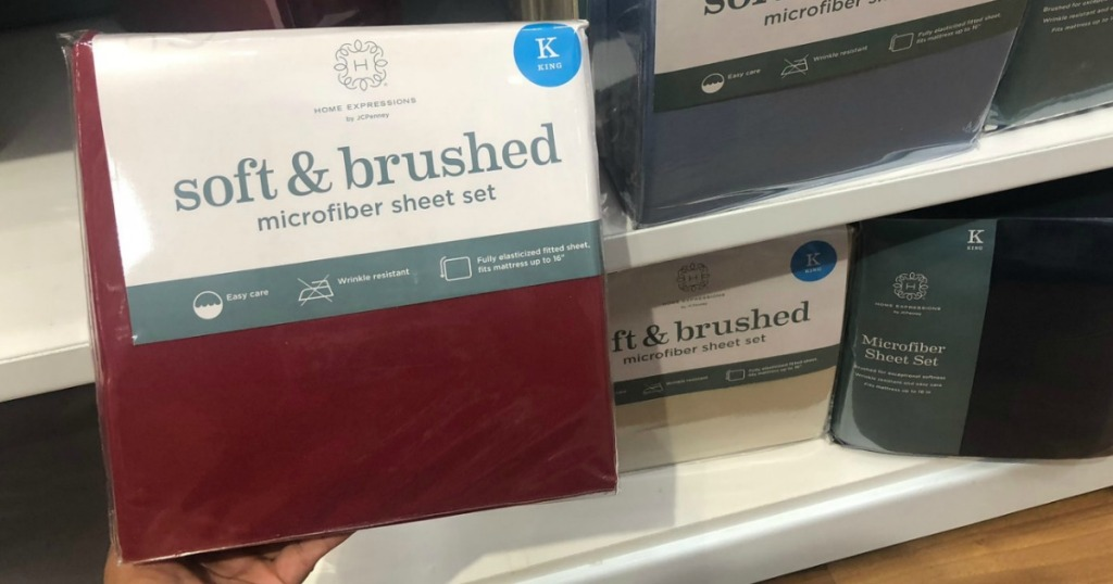 JCPenney brand sheet set in burgundy color in front of shelf of King size sheets