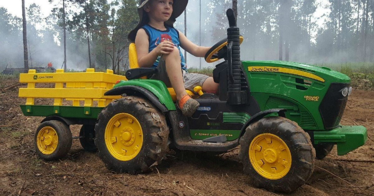 boy riding John Deere Peg Perego Tractor in woods