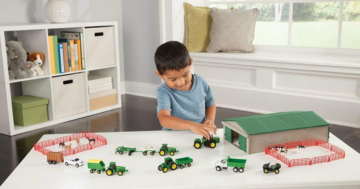 little boy playing with john deere farm set