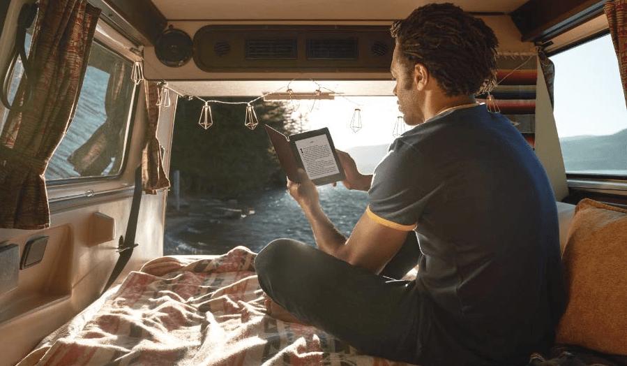 man holding Kindle eReader in camping trailer