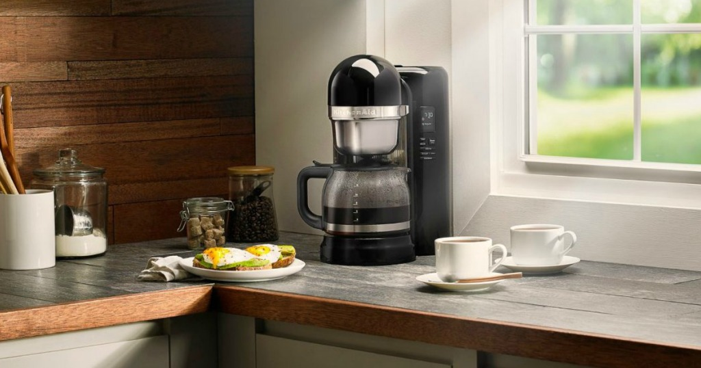 KitchenAid coffeemaker with coffee mugs next to it