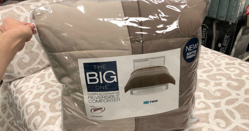Beige and brown down alternative comforter in package on coordinating store display bed