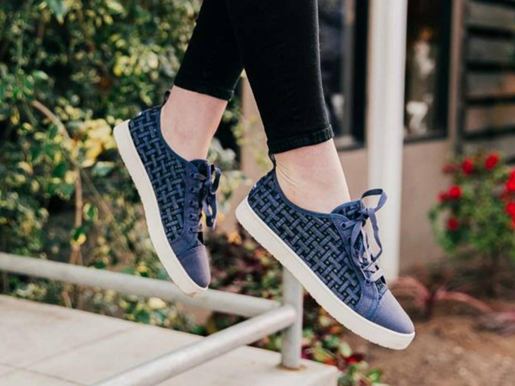 women's legs dangling with blue denim shoes