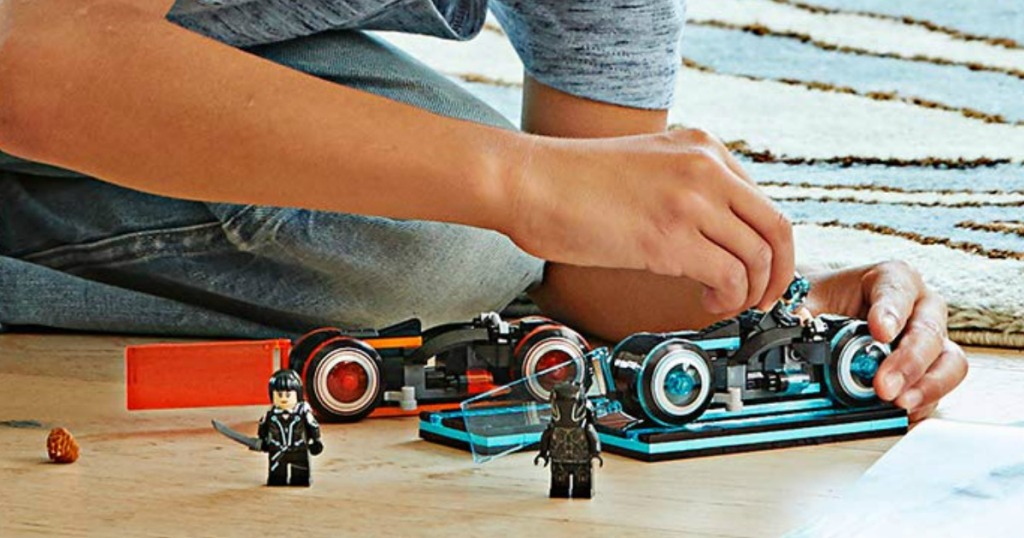 boy playing with LEGO TRON building set