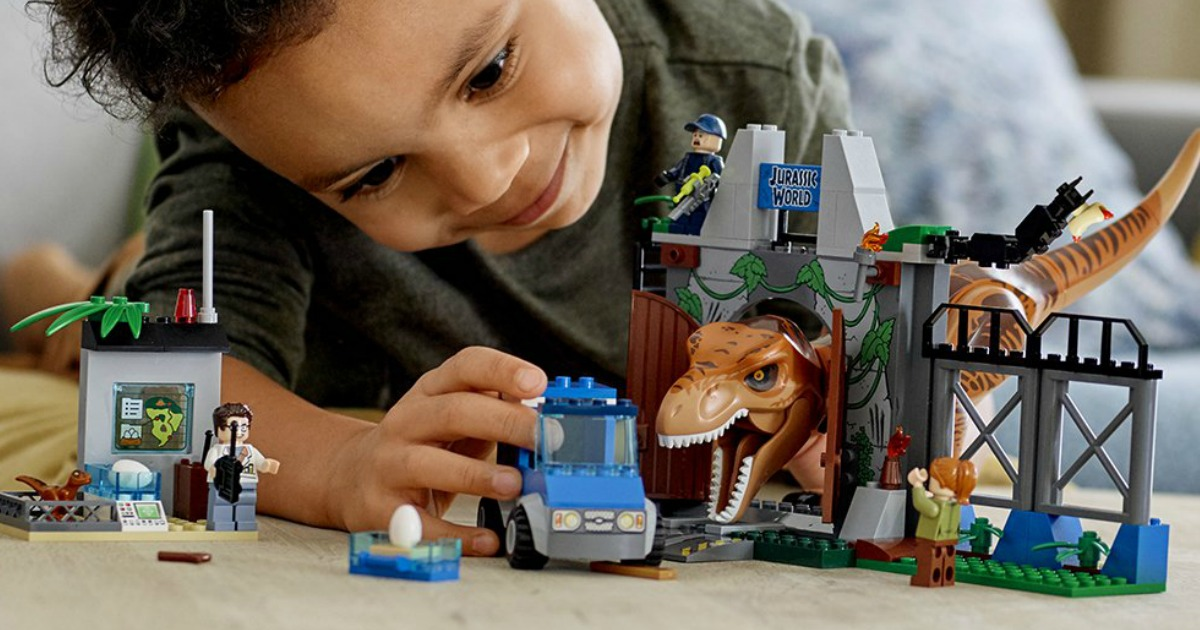 boy playing with a LEGO set, truck, and dinosaur