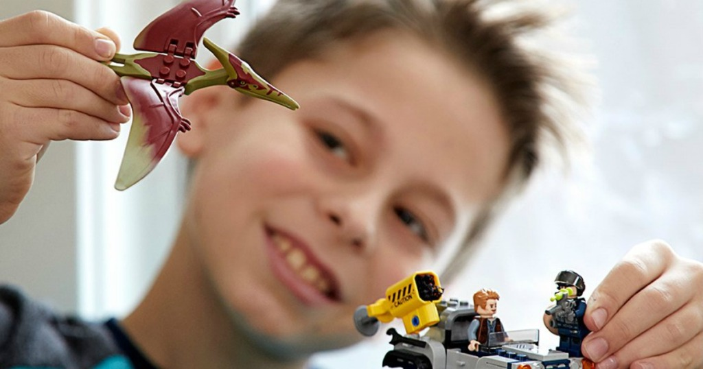 Boy playing with LEGO Jurassic World building set