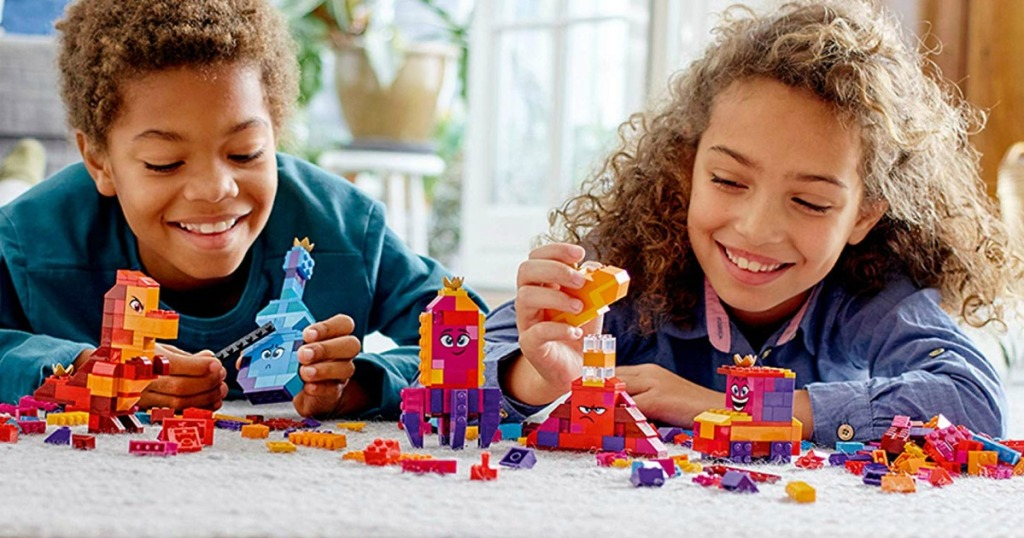 Two kids playing with a LEGO Movie 2 Queen Set