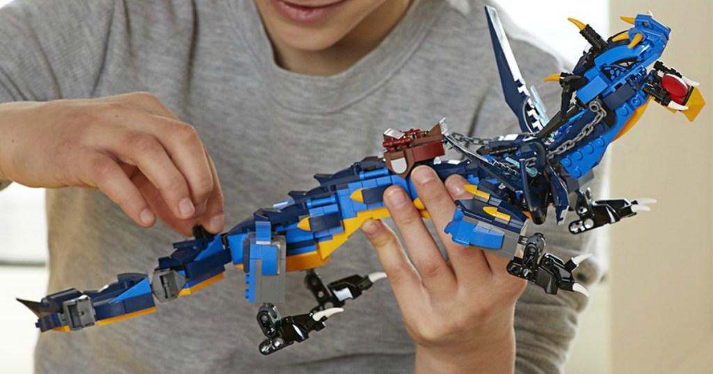Boy playing with Blue dragon LEGO set