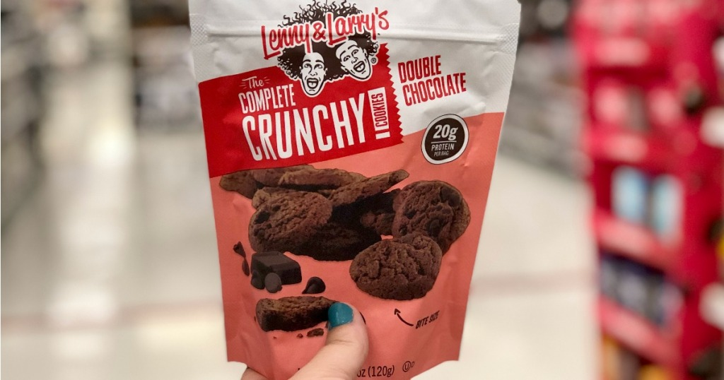 hand holding up Lenny & Larry Complete Crunchy Pouch in store aisle