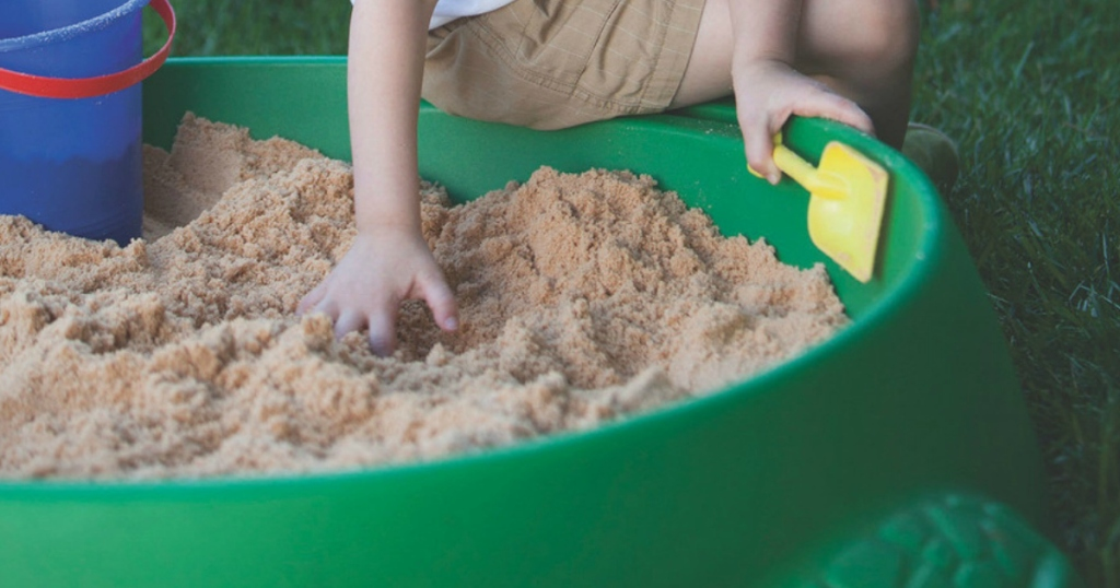 Kid playing in green sandbox with bucket and shovel