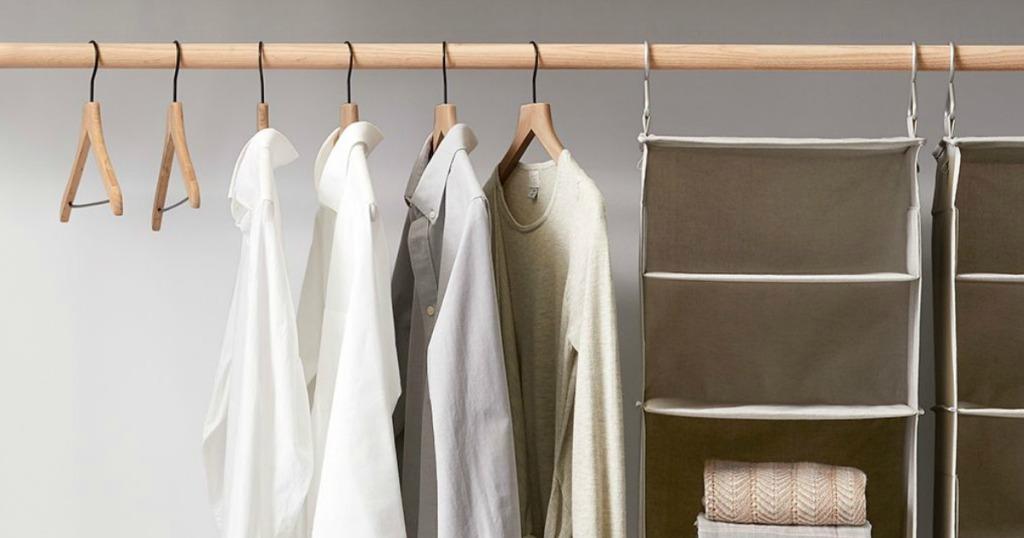 closet with wood hangers and shirts hung on them