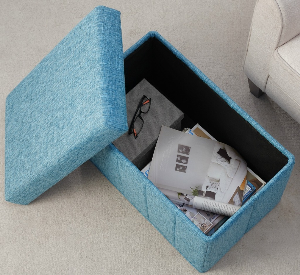 Blue denim fabric storage ottoman with papers and glasses being stored