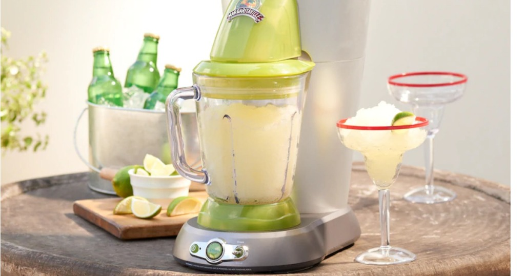Margaritaville frozen drink maker on counter near margaritas and limes