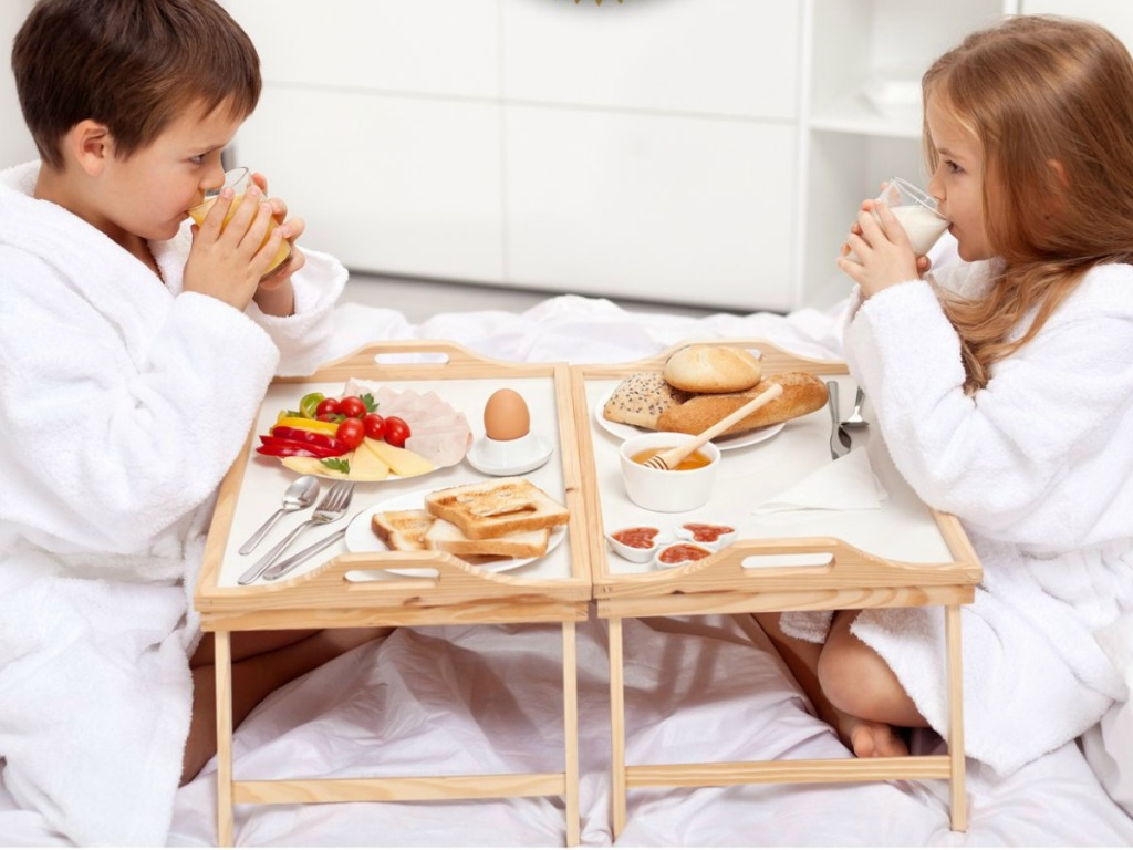two kids eating on a bed