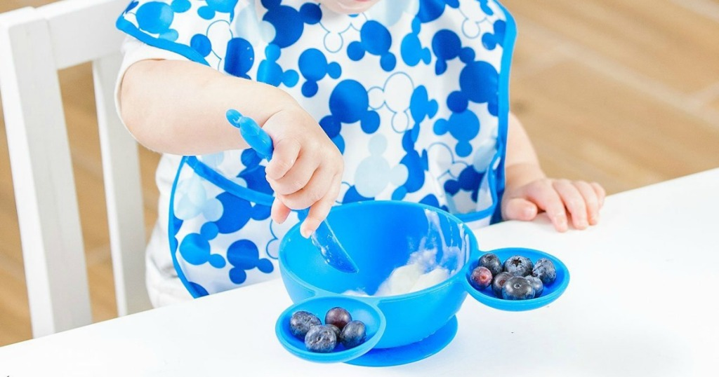 toddler eating blueberries and yogurt in a Mickey silicone bowl