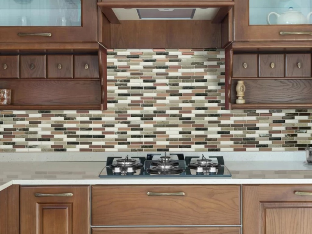 Milenza Taddio Peel & Stick Decorative Mosaic Wall Tile Backsplash in kitchen with stove and cabinets