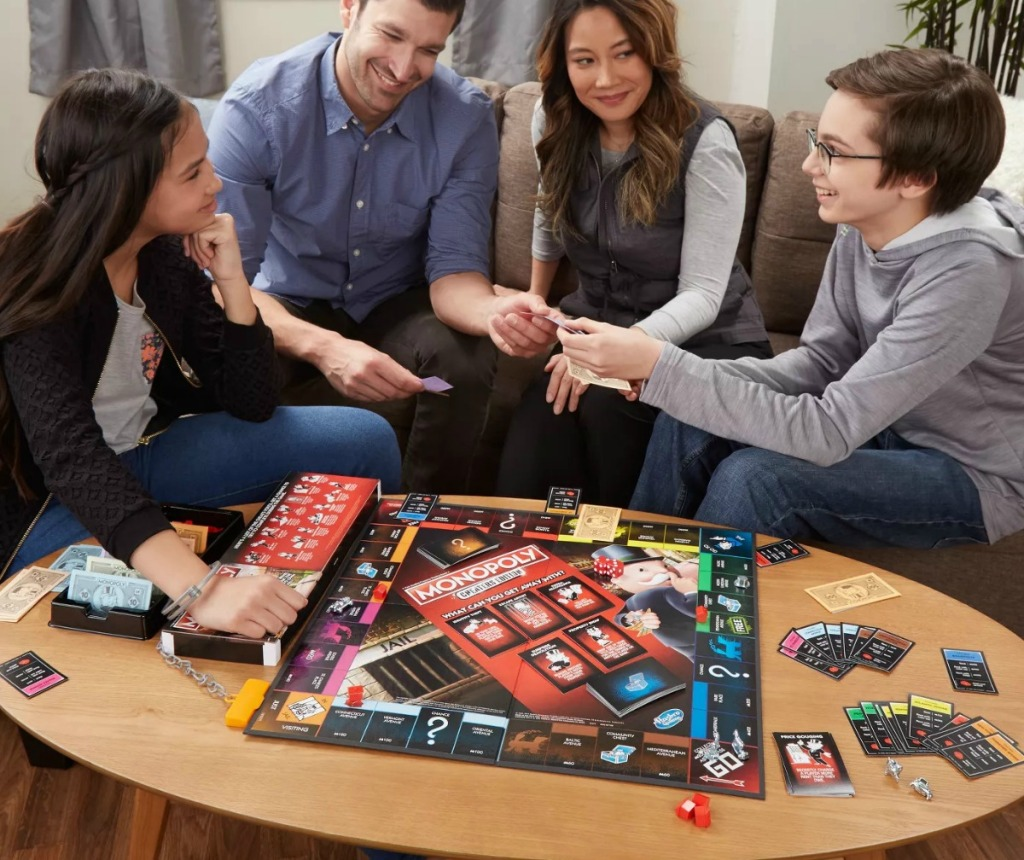 Family playing Monopoly Cheaters Edition on their coffee table