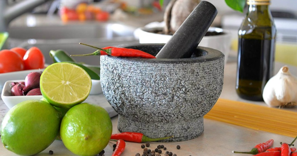 Morter and Pestle in a kitchen with limes, oil, peppers