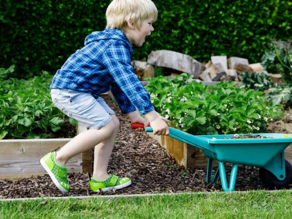 boy helping in garden wearing gator shoes