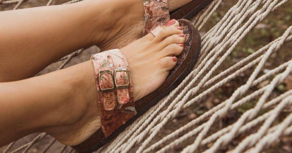 Woman wearing Blush Daisy Terra Turf Sandals in hammock