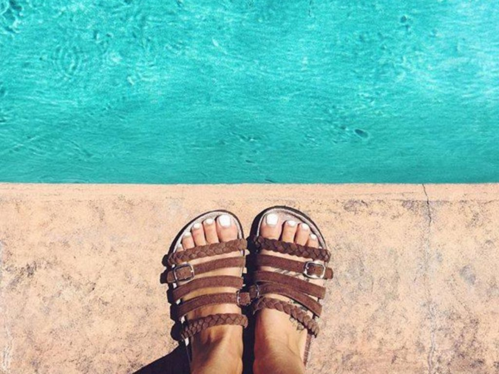Woman wearing Muk Luks Chocolate Chip Terri Terra Turf Slide Sandals by poolside