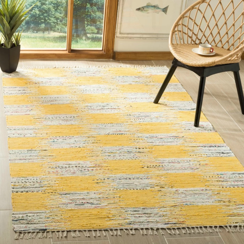 Yellow & gray checkered woven rug in living room with wicker chair