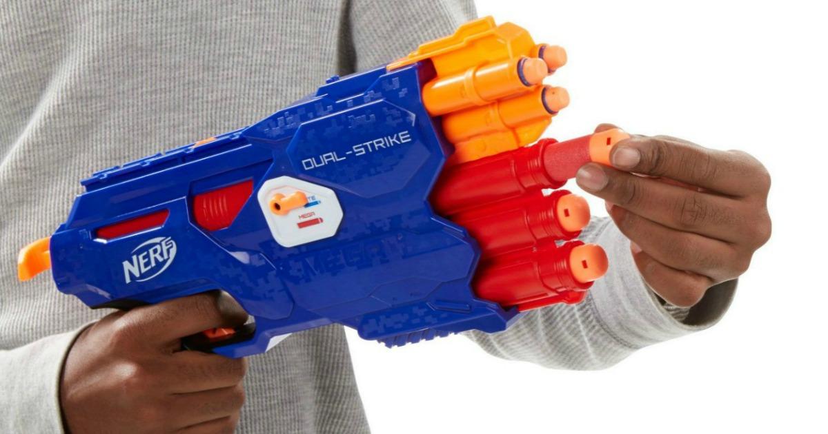 boy loading dart into NERF Dual-Strike blaster gun