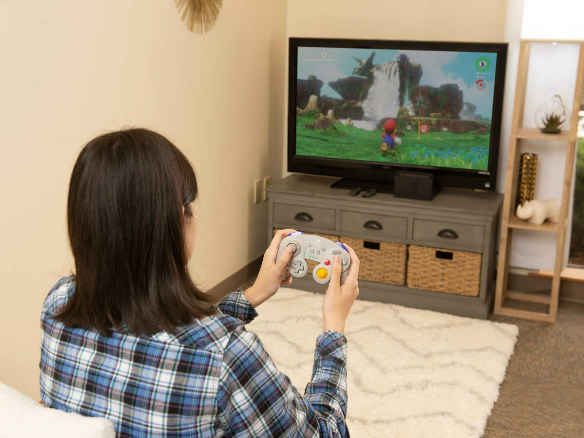 woman using gray switch controller to play video game