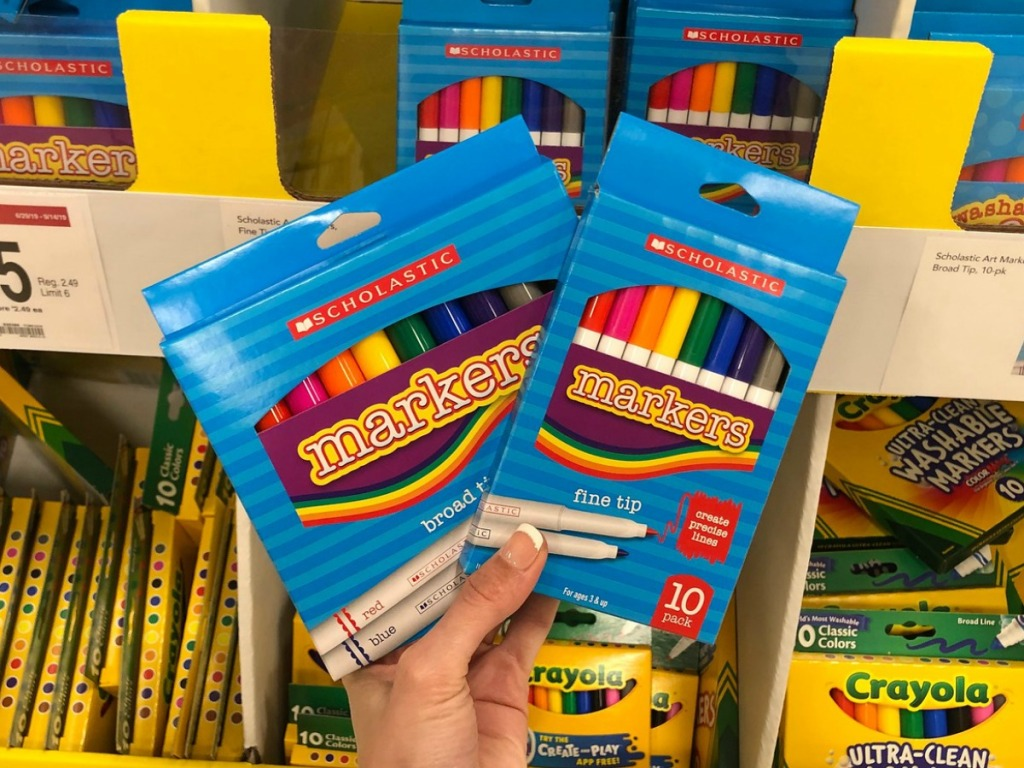 Hand holding two packs of Scholastic markers