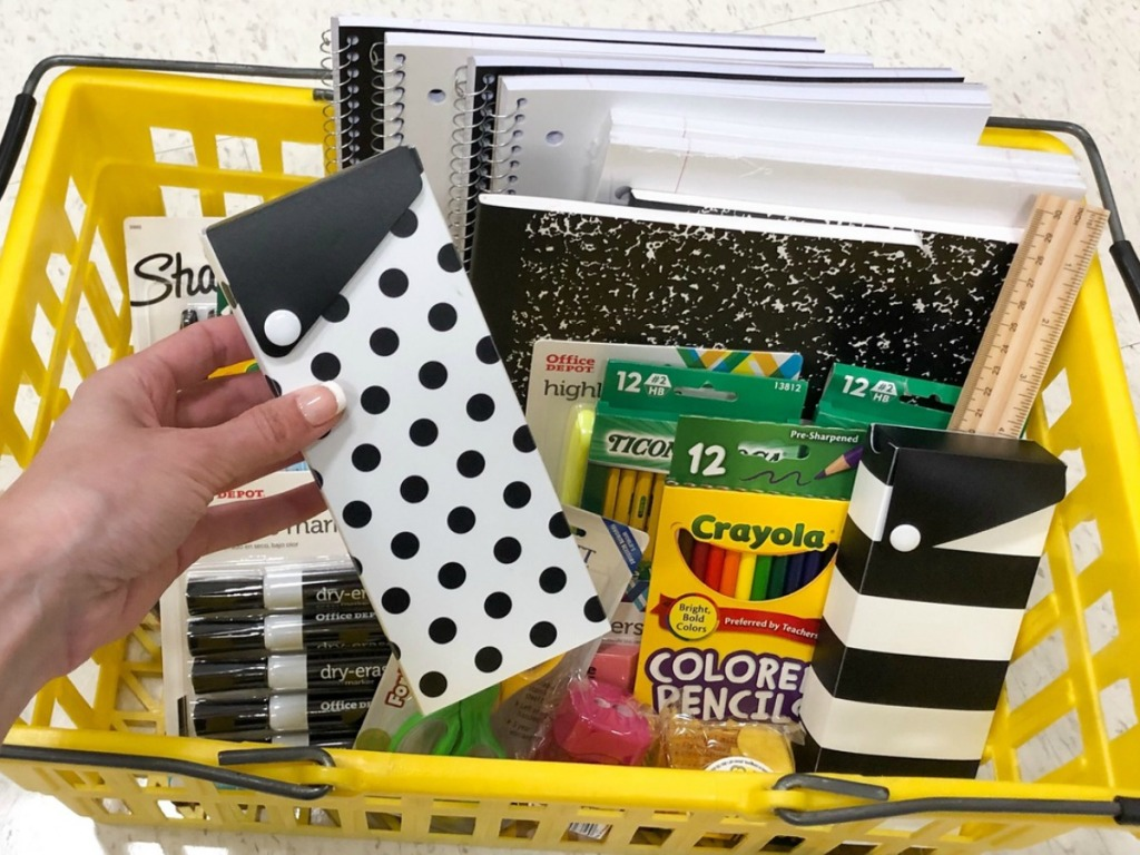 Patterned pencil boxes held up over a basket of supplies