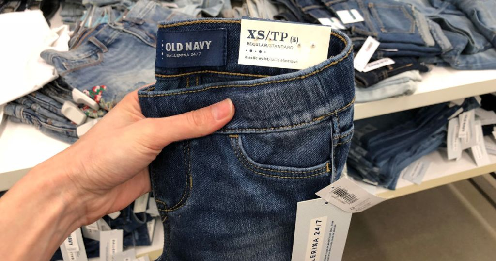 old navy girls jeans held up by woman hand in store
