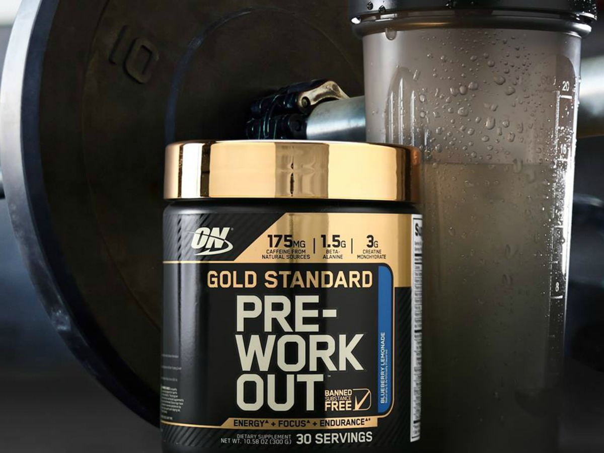 Optimum Nutrition Gold Standard Pre-Workout Powder in Blueberry Lemonade with shaker bottle and weights in background