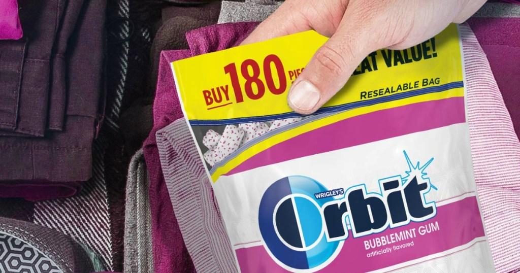 hand grabbing Orbit gum bag