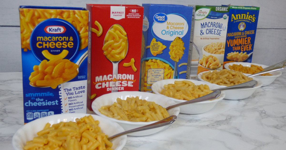 boxed macaroni and cheese lineup behind five bowls of macaroni and cheese