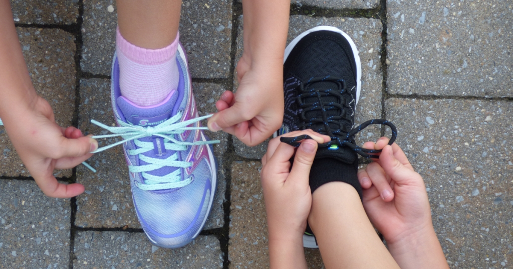 2 kids tying shoes