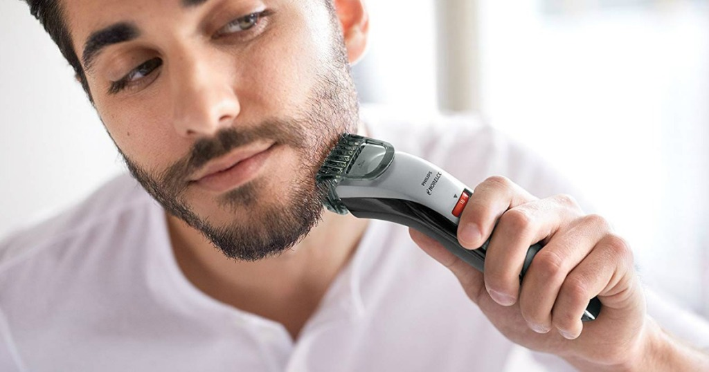 Man trimming facial hair with rechargeable trimmer