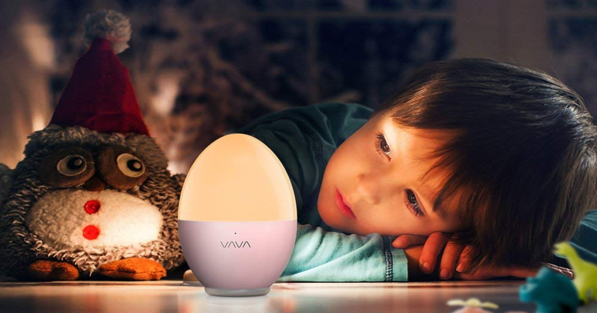 VAVA kids, egg shaped night light in pink sitting on a table with a child laying their head down on the table to the right of it and a stuffed owl sitting to the left.