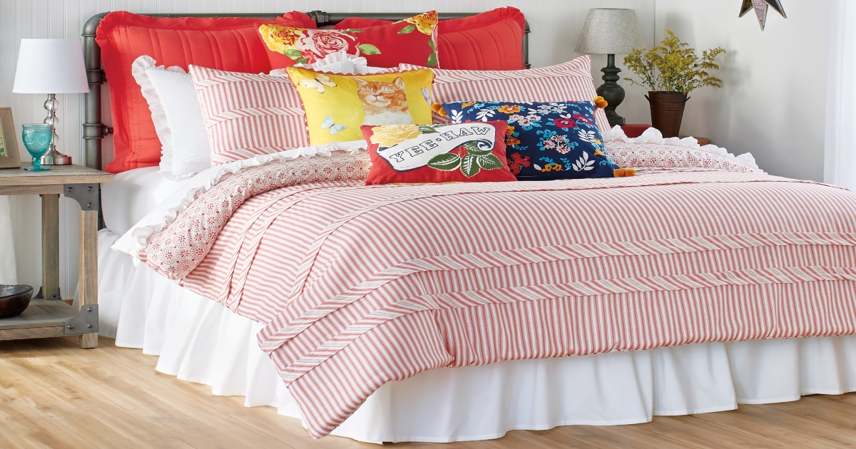 Pioneer Woman Striped red comforter on a fully made up large size bed with many decorative throw pillows.