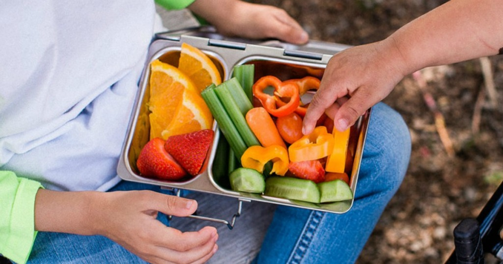 Kids sharing PlanetBox stainless steel lunchbox filled with fruit and veggies