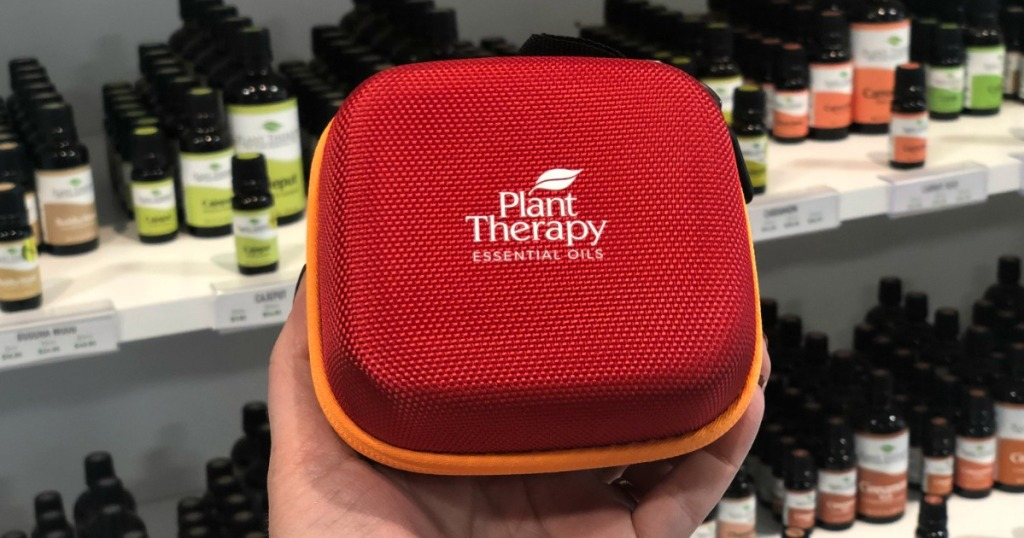 Plant Therapy Summer Grab Bag being held in front of essential oils