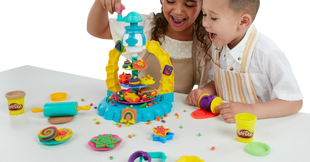Children playing with a Play-Doh Kitchen Creations Sprinkle Cookie Surprise Play Set with 5 Cans of Play-Doh