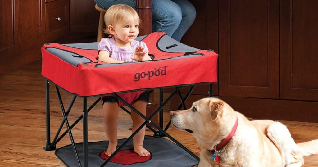 Baby sitting in portable playpod