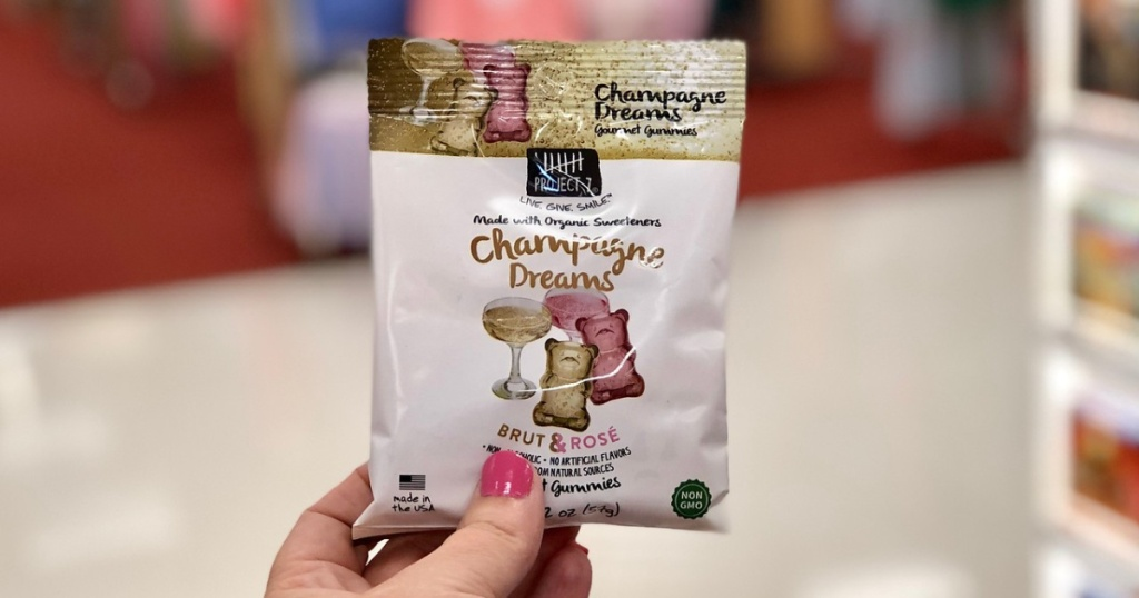 woman holding project 7 champage gummies at target