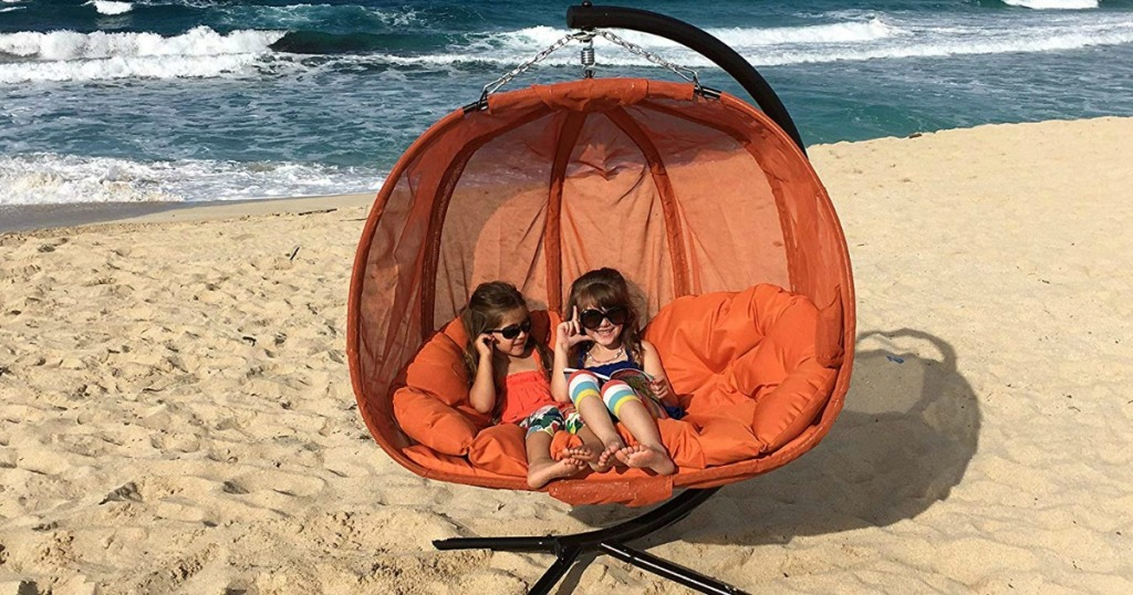 two kids sitting on pumpkin chair at the beach