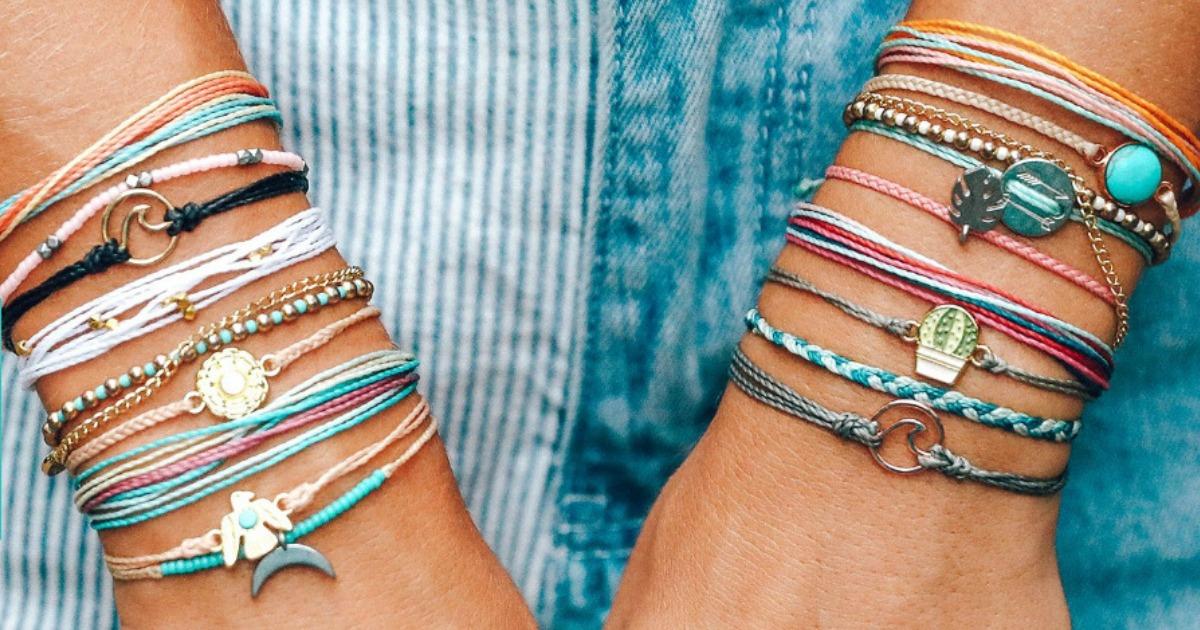 woman's wrists adorned with numerous bracelets