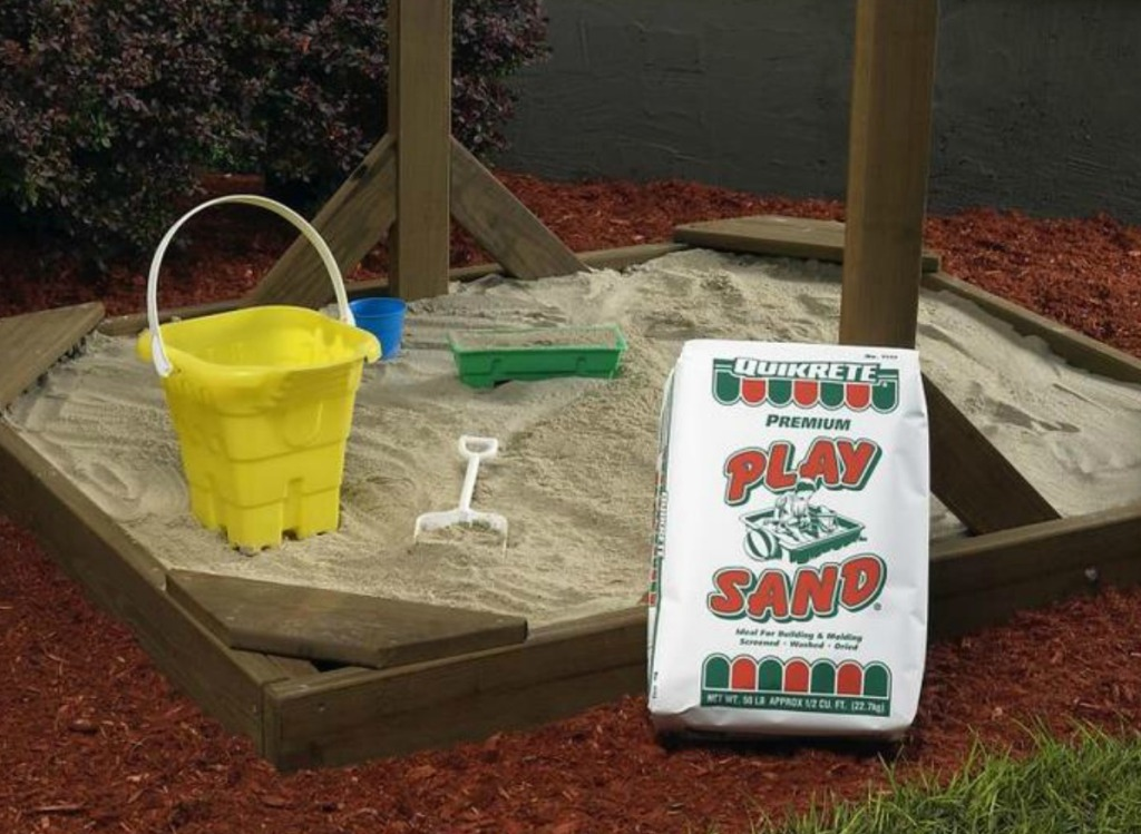 Large bag of play sand in front of a full size sand box with accessories