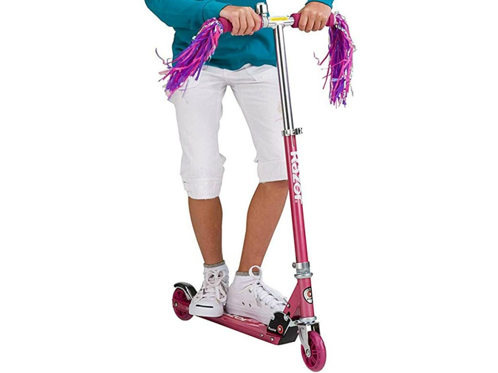 kids standing on pink razor scooter
